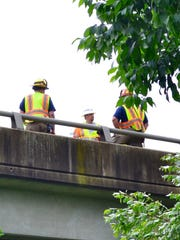 Emergency personnel and workers from the Virginia Department of Transportation stand on an Interstate 81 bridge as an accident scene is cleared Friday morning.