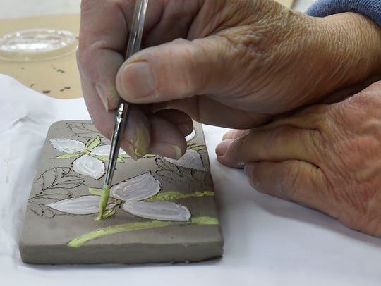 Jane Moeller paints trilliums on her clay tile at the