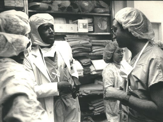 Dr. Ben Carson (second from left) talks with other surgeons outside an operating room at Johns Hopkins in 1988. Carson was photographed as part of a profile that the Detroit Free Press did on the Detroit native on May 15, 1988.