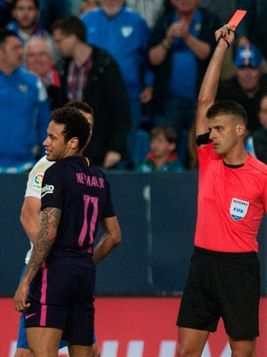 The referee shows a red card to Barcelona's Neymar.