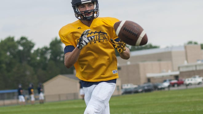 A player catches a football Friday, Aug 12, during practice at Port Huron Northern High School.