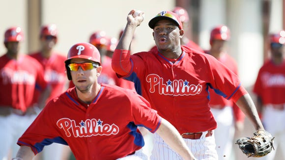 Philadelphia Phillies Maikel Franco, right, chases teammate Clete Thomas during a drill in a spring training baseball practice Wednesday, Feb. 19, 2014, in Clearwater, Fla. (AP Photo/Charlie Neibergall)