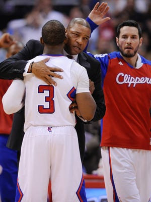 Clippers coach Doc Rivers hugs point guard Chris Paul during an April playoff game, shortly after Donald Sterling's racist remarks were leaked.
