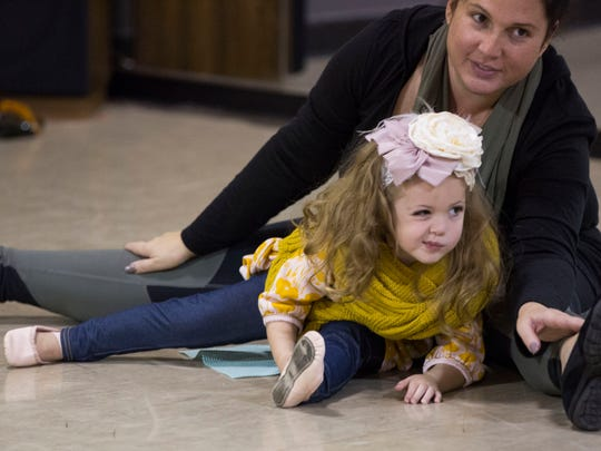 Tierstiana Buie, 2, stretches and touches her toes with her mom, Mandi Buie, while at a Mommy and Me class at D'Alto Studio in Evansville Tuesday night.