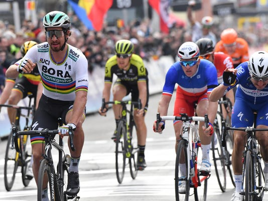 Slovakia's Peter Sagan, left, from the Bora-Hansgrohe team crosses the finish line to take first place in the Gent-Wevelgem cycling race in Wevelgem, Belgium on Sunday, March 25, 2018. (AP Photo/Geert Vanden Wijngaert)