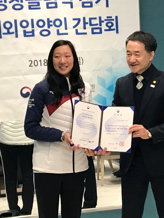 Neunghoo Park, South Korean minister of health and welfare, right, names Marissa Brandt an honorary ambassador for adoptee birth family searches Sunday, Feb. 25, 2018, during a lunch in Gangneung, South Korea. Brandt, adopted as a baby by Greg and Robin Brandt of Vadnais Heights, Minnesota, played for South Korea's historic combined women's team under her birth name, Park Yoonjung. (AP Photo/Teresa M. Walker)