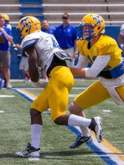 Derrick Milton (left) takes a handoff during McNeese State's spring game. Milton, a former standout at Pineville, transferred to the Cowboys from Mississippi State.