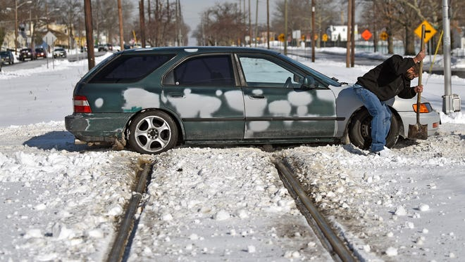 Alfredo Nieves of Vineland tries to dig his car free from snow on the railroad tracks at S.W. Boulevard and Cherry Street on Monday.