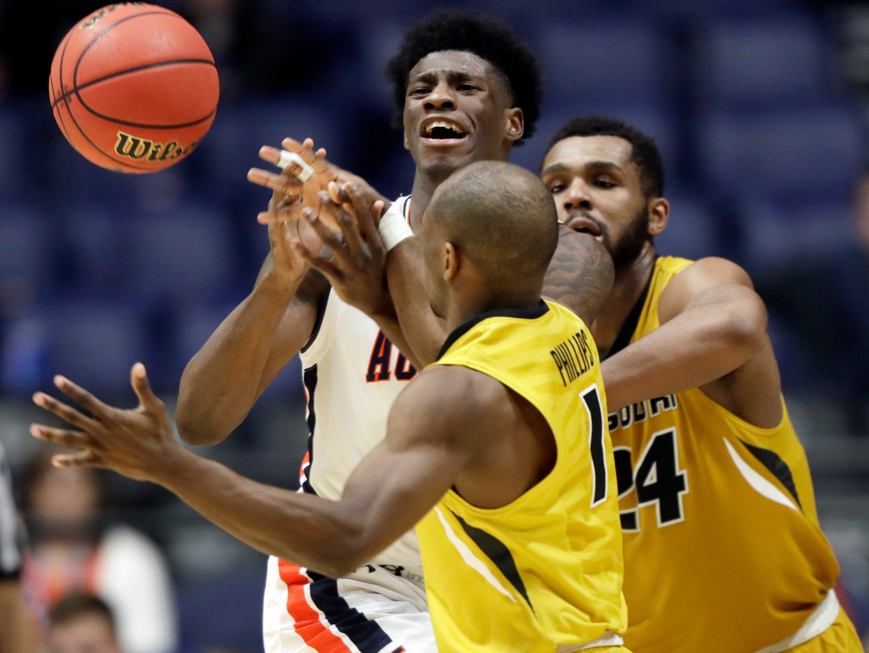 Auburn forward Danjel Purifoy, left, loses the ball as he is defended by Terrence Phillips (1) and Kevin Puryear (24) during the second half of an NCAA college basketball game at the Southeastern Conference tournament Wednesday, March 8, 2017, in Nashville, Tenn.