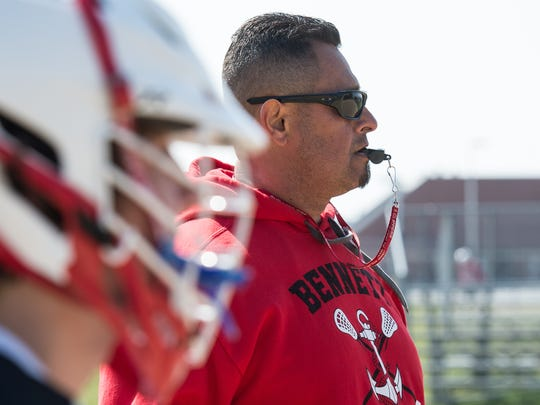 James M. Bennett lacrosse coach Milt Rodriguez watches as his players practice a drill on Tuesday, April 10, 2018.