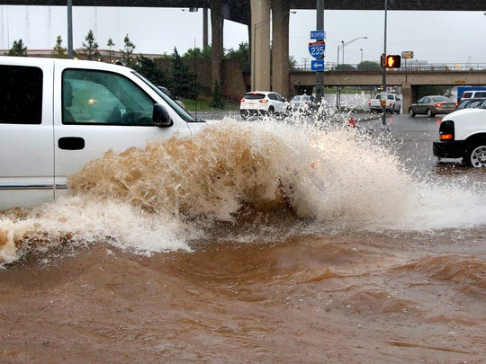 A truck creates a wave as it forces its way through high water on May 23, 2015, in Oklahoma City.