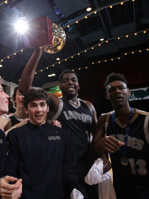 Lourdes' James Anozie hoists the gold ball after defeating Tappan Zee 42-38 in the Section 1 Class A boys championship basketball game at the Westchester County Center in White Plains on Sunday, March 5, 2017.