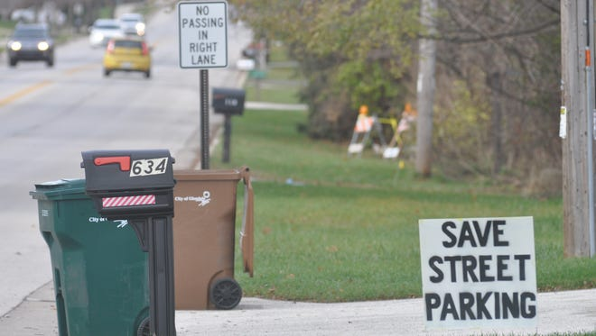 """Bender Road resident Jeanne Wesley has posted a """"Save street parking"""" sign for her front yard. Wesley and other Bender Road residents oppose the elimination of parking in favor of new bicycle lanes."""