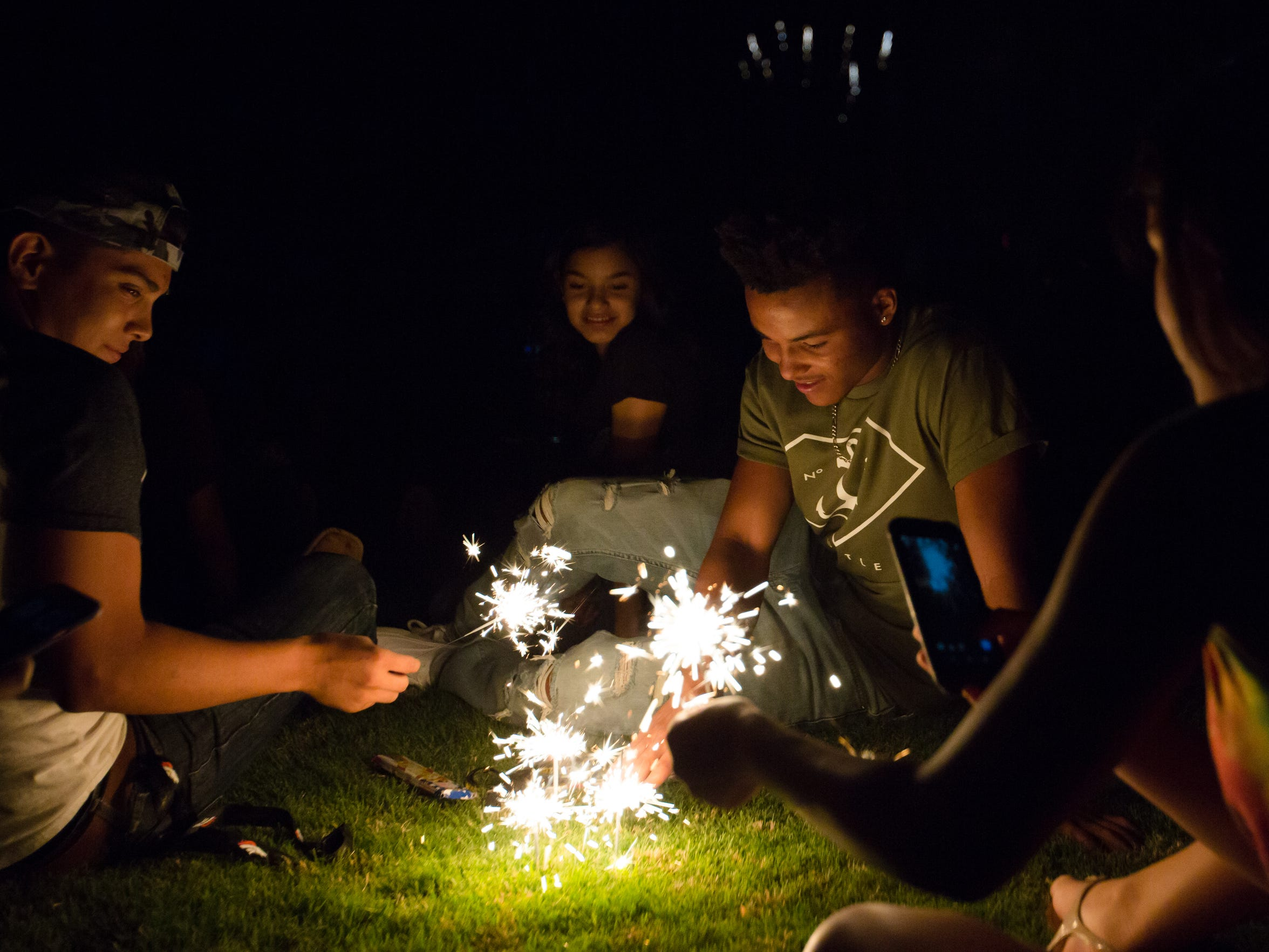 Fifteen year old Nathaniel Adams, and Savion Russell, 16, join friends as they play with sparklers during the Fourth of July celebration at the Field of Dreams, last year. The county urges residents  be aware of fireworks rules and regulations. If purchasing fireworks to shoot them off a safe area.