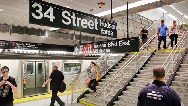 Travelers walks downstairs to the No. 7 subway line at the 34th Street and 11th Avenue station, New York City's first new station in a quarter-century, Sept. 13, 2015.