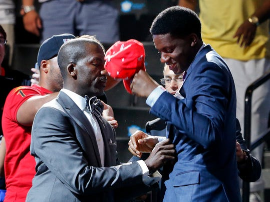 CORRECTS SPELLING OF DRAFTEE'S LAST NAME TO CAPELA - Clint Capela, right, of France, is handed a Houston Rockets cap after being selected 25th overall by the Rockets during the 2014 NBA draft, Thursday, June 26, 2014, in New York. (AP Photo/Jason DeCrow)