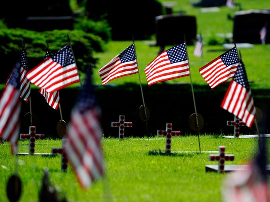 Flags fly for veterans at markers in Lansing's Evergreen Cemetery at the city of Lansing's Memorial Day ceremony, May 22, 2015.