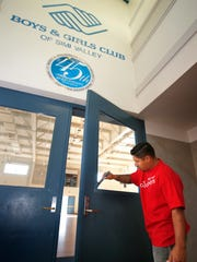 Wells Fargo's Simi Valley branch manager Rudy Alaniz works on painting the door to the gym at the Boys & Girls Club in Simi Valley as part of the United Way's Day of Caring on Saturday.