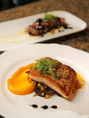 Salmon with butternut squash puree, sautéed cherry tomatoes, white corn and sweet rainbow char is one of the entrées at Cocovin in Oxnard.