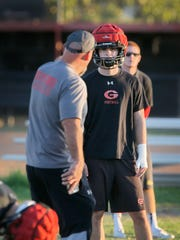 """Grace Brethren linebacker/running back Joshua Henderson listens to instructions from his father and the Lancers head coach Josh Henderson during a practice. """"As a father and coach, you can sometimes be too hard on your son. I'm always working on that. I'm trying to get this down just right,"""" says dad about coaching his son."""