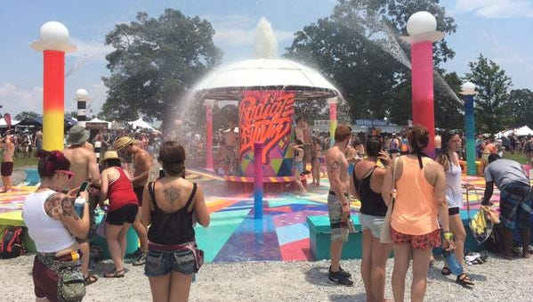 Bonnaroonies, yes, that's their official title, cool off under a sprinkler to avoid the heat during the 14th Bonnaroo Music & Arts Festival inManchester, TN