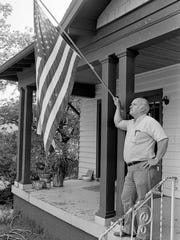 V.J. (Vince) Richards, president of Richards Construction Co., 2511 12th Ave. S., doesn't confine his flying of the flag to July Fourth as he looks on July 3, 1984. Richards, a Korean War veteran, has flown the flag in front of his place daily since 1966.