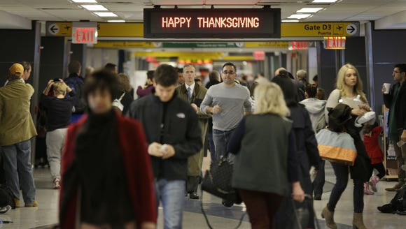 """Travelers walk under a sign reading """"Happy Thanksgiving"""""""
