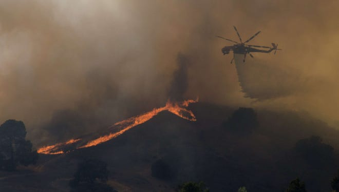 A firefighting helicopter dumps water on a brush fire near Highway 101 north of Los Angeles.