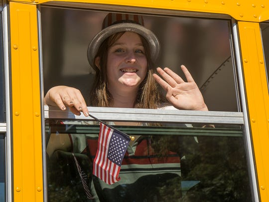 Olivia White waves from a Plymouth-Canton School Bus, operated by Durham School Services.