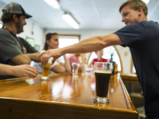 Ben Linehan, co-owner with Anne Lineman of Brocklebank Brewery in Tunbridge, right, serves a patron over an already-sampled glass of the Class IV American black ale on Friday, July 15, 2016.
