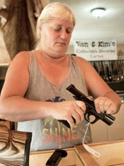 G & G Retailers owner Kim Smithe demonstrates the correct way to handle a handgun in this Aug. 28, 2017, photo. Smithe and her father, Glen, have owned the Davenport, Iowa, gun shop for 35 years.