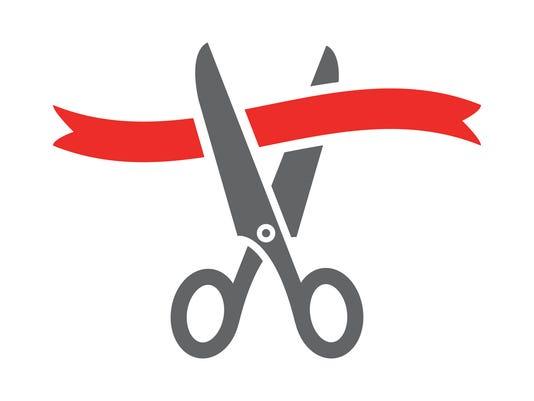 Scissors cutting red ribbon.