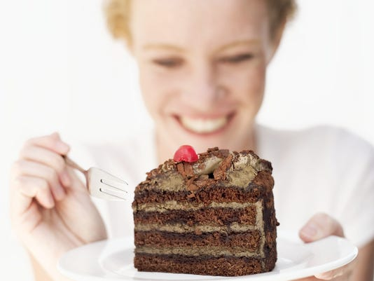 smiling woman about to eat a slice of cake