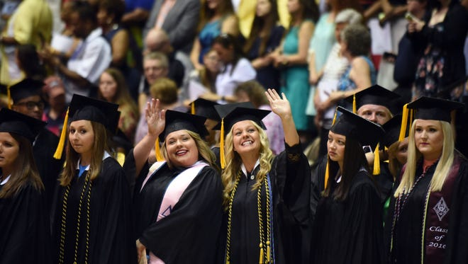 Southern Miss graduates wave to family and friends during the spring commencement ceremony.