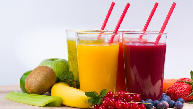 Colorful fresh pressed fruit green, yellow, oragne and red juices with fresh fruits and berries on white background