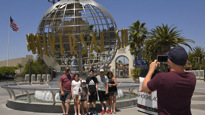 A family has their picture taken at Universal CityWalk on Thursday near Universal City. The tourist attraction, which had been closed due to the coronavirus outbreak recently reopened.