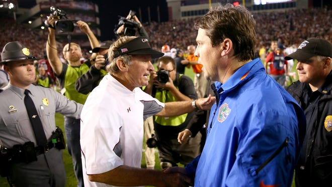 South Caroline coach Steve Spurrier, and FLorida Gators coach Will Muschamp are both on the hot seat. Spurrier, who built the Gators into a power as head coach in the 90s, could be coaching his last game in the Swamp. In this picture, they shake hands following last year's game, which South Caroline won.