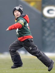 Austin Beauchamp, 6, of De Pere races off the field following the opening kickoff of the Green Bay Packers' 38-10 win over the Seattle Seahawks at Lambeau Field.
