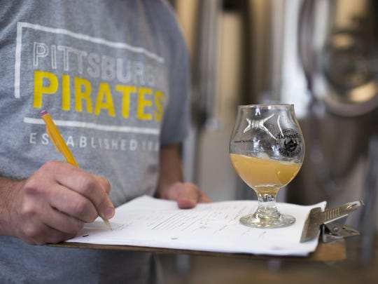 Brewmaster Jason Weissberg takes notes on a batch he's working on inside Assawoman Bay Brewing Co. Thursday morning in Ocean City.