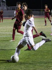 Erick Serrano shooting the ball into the goal. The