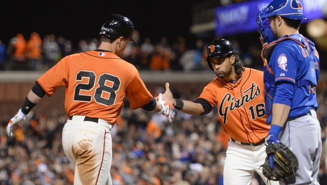 San Francisco Giants catcher Buster Posey, left, and center fielder Angel Pagan (16) celebrate after both scored on Posey's two-run home run in the eighth inning Friday night. Mets catcher Travis d'Arnaud can only watch the celebration.