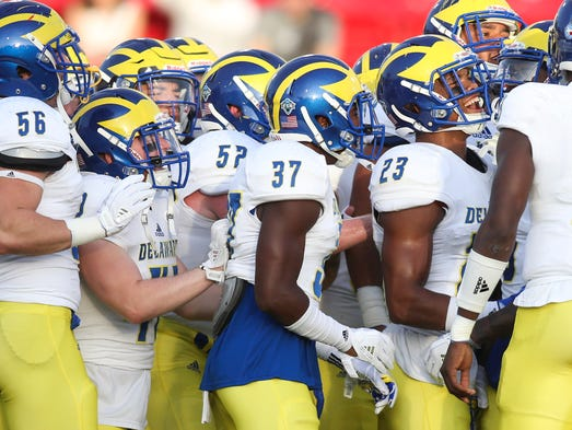 The Blue Hens gather around each other as they prepare