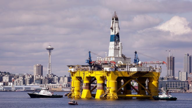 An oil drilling rig is towed toward a dock in Elliott Bay in Seattle in May 2015. Royal Dutch Shell is outfitting it for Arctic oil exploration.