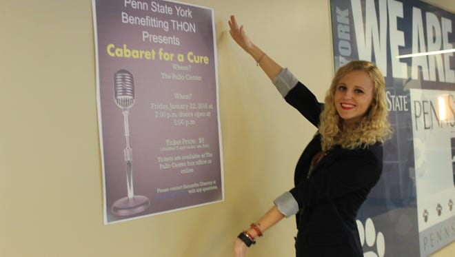 Samantha Glancey, a sophomore at Penn State York and a member of the campus THON group, shows off a poster for the upcoming fundraiser Cabaret for a Cure. The fundraiser has been rescheduled to Jan. 29 because of the impending snow storm.