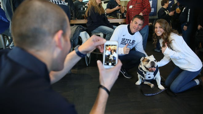 Michael Kaltenmark (left) of Indianapolis, the handler for Blue III, takes photos of Joel Cohen and his daughter, Caroline Cohen, a student at Butler, at Evolution Gastro Pong. The English bulldog is the mascot for Butler University.