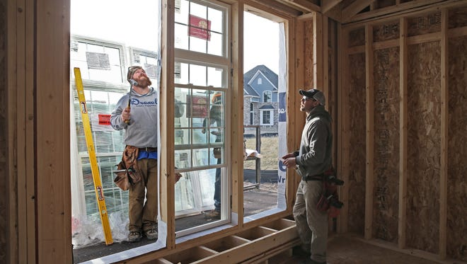 Kyle Aulenbacher (from left), Clay Parulski and Mitch McGuire work installing windows in a home under construction for Westridge Builders on Tamarack Trail in Menomonee Falls.