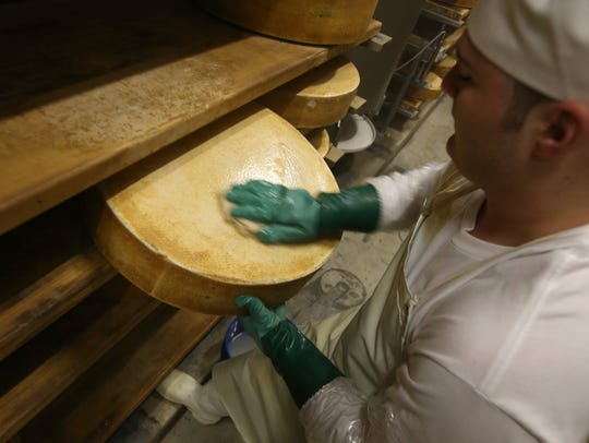 Cheesemaker Dylan Bush of Perry wipes down every wheel