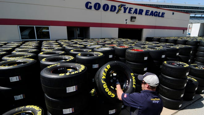 Brayden Wienke stacks Goodyear tires at Texas Motor Speedway in Fort Worth, Texas, in April. Goodyear is well-known for supplying race tires. Its third-quarter earnings were higher than analysts forecast, despite revenue and sales drops.