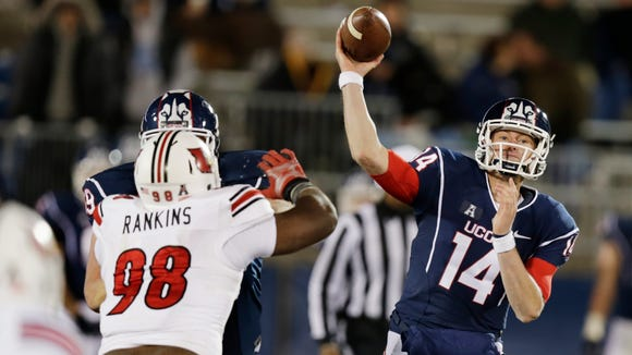 Connecticut quarterback Tim Boyle (14) passes as he is pressured by Louisville defensive end Sheldon Rankins (98) during the second half of an NCAA college football game in East Hartford, Conn., Friday, Nov. 8, 2013. Louisville defeated Connecticut 31-10. (AP Photo/Charles Krupa)