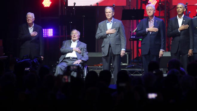 Former Presidents from right, Barack Obama, Bill Clinton, George W. Bush, George H.W. Bush and Jimmy Carter place their hands over their hearts for the national anthem on stage at the opening of a hurricanes relief concert in College Station, Texas, Oct. 21, 2017. All five living former U.S. presidents joined to support a Texas concert raising money for relief efforts from Hurricane Harvey, Irma and Maria's devastation in Texas, Florida, Puerto Rico and the U.S. Virgin Islands.
